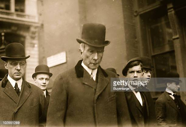 Standard Oil Company founder John Davison Rockefeller walks on a New York city street amongst an unidentified group 1908