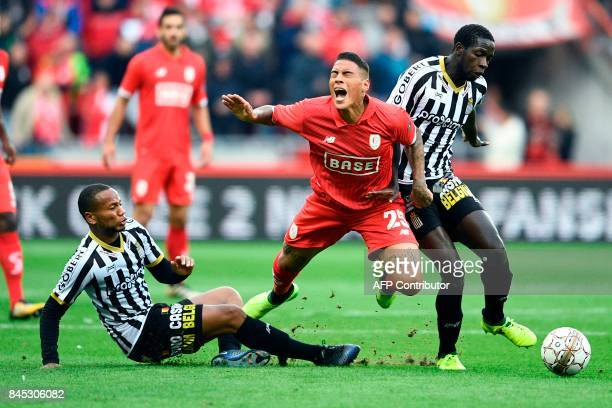 Standard's Carlinhos falls as he vies for the ball with Charleroi's Marco Ilaimaharitra and Charleroi's Christophe Diandy during the Jupiler Pro...