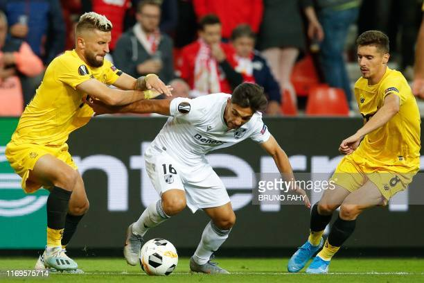 Standard's French defender Nicolas Gavory Vitoria's Portuguese midfielder Rochinha and Standard's Bosnian defender Gojko Cimirot fight for the ball...