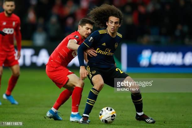 Standard's Gojko Cimirot and Arsenal's Matteo Guendouzi fight for the ball during a soccer match of Belgian team Standard de Liege against English...