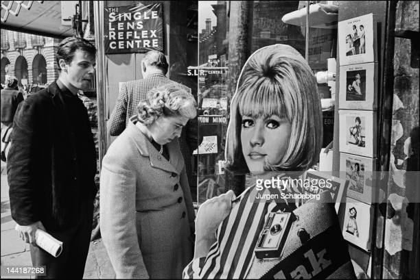 A standee advertisement for Kodak cameras featuring the 'Kodak Girl' in central London 1965