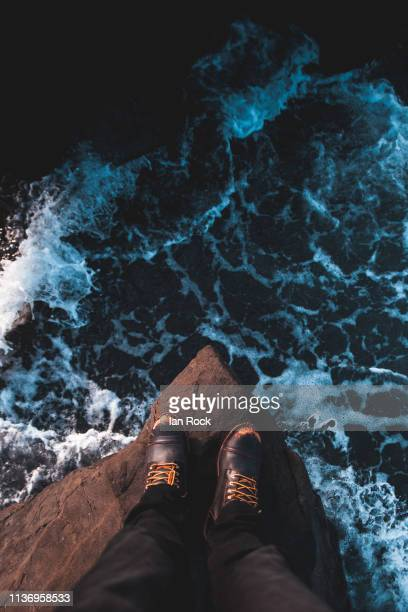 standing above the rough sea - leap of faith stock photos and pictures