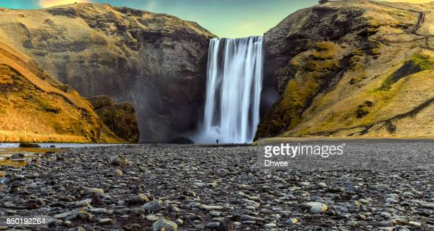 Standing Alone In Front Of The Majestic Of Skogafoss Waterfall