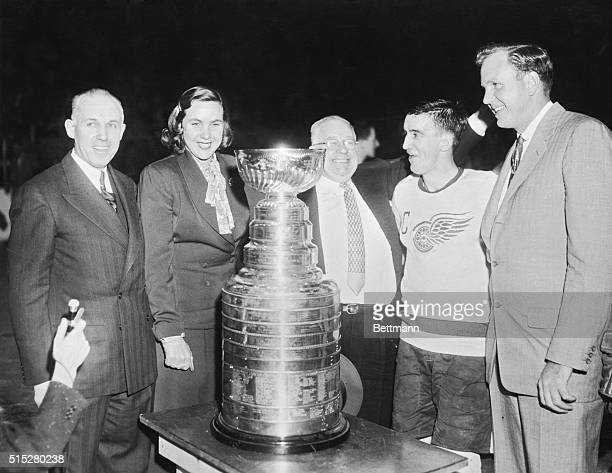 Standing around the Stanley Cup after Detroit's win are left to right NHL President Clarence Campbell Marguerite Norris part owner of the Red Wings...