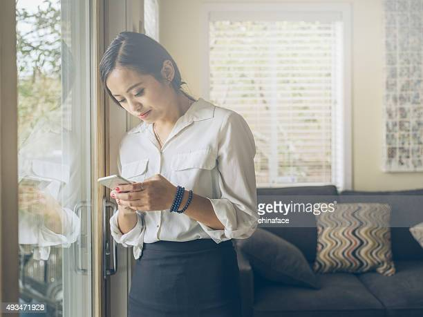 standing asian woman checking phone messages