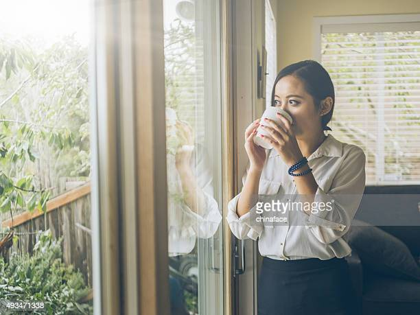 standing asian woman looking out   window at home