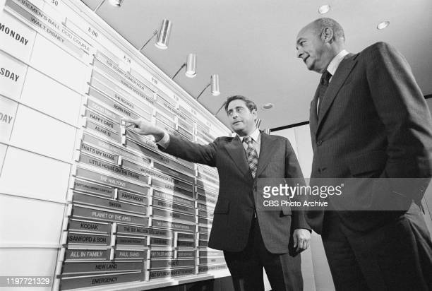 Standing at a television network program board from left Fred Silverman head of CBS Programming and Robert D Wood President CBS Television Network...