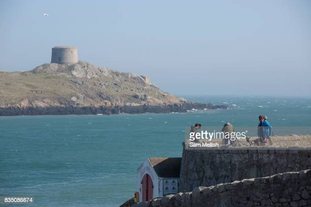 Standing at Coliemore Harbour cyclists overlook Dalkey Island on 08th April 2017 in County Dublin Republic of Ireland Dalkey is one of the most...