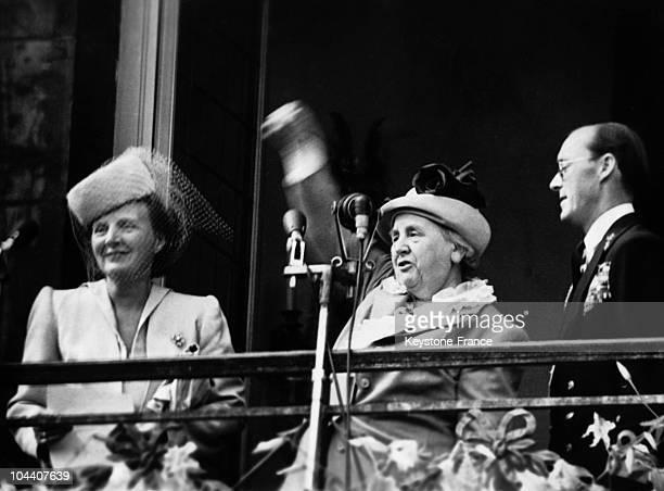Standing between her daughter the new queen Princess JULIANA and Prince BERNHARD Queen WILHELMINA of Holland says her goodbyes as the sovereign from...