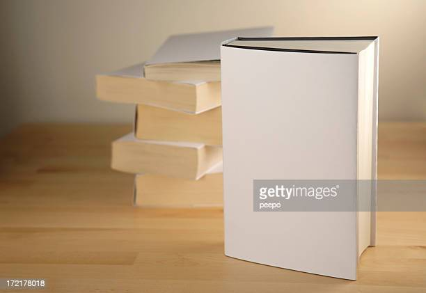 Standing book with blank cover with books stacked behind.
