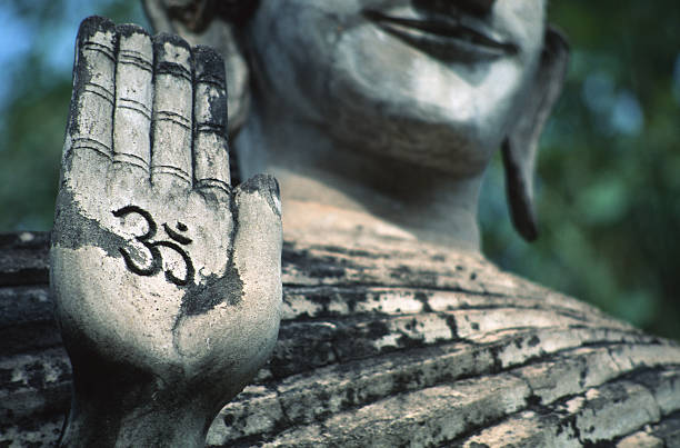 A Standing Buddha Holds Up A Hand Inscribed With The Mantra