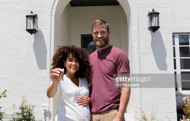 staande door echtgenoot, zwangere vrouw houdt sleutels tot nieuw huis - voor stockfoto's en -beelden
