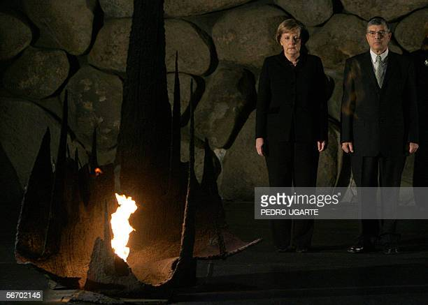Standing close to the Eternal Flame German Chancellor Angela Merkel stands with Avner Shalev the chairman of Yad Vashem Holocaust museum during a...