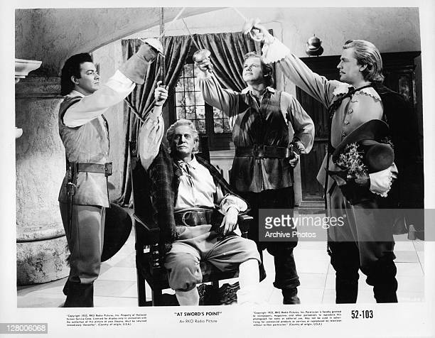 Standing from left, Cornel Wilde, Alan Hale Jr, and Dan O'Herlihy, along with an unidentified, seated actor raise their swords in a scene from the...