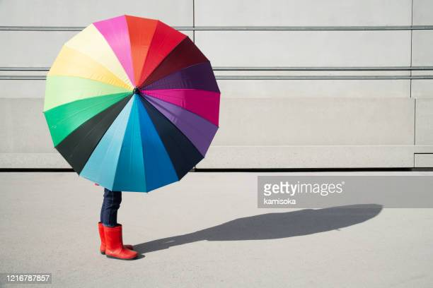 standing girl with multicolored umbrella in front of a concrete wall - vitality stock pictures, royalty-free photos & images
