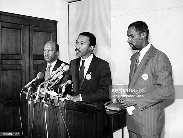 Standing in between two other men Kweisi Mfume delivering a speech at the podium 1990
