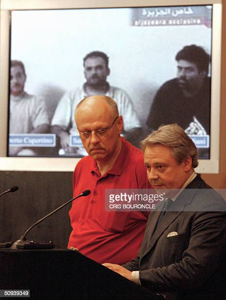 Standing in front a projected image showing three Italian hostages from left to right Umberto Cupertino Salvatore Stefio and Maurizio Agliana Italian...