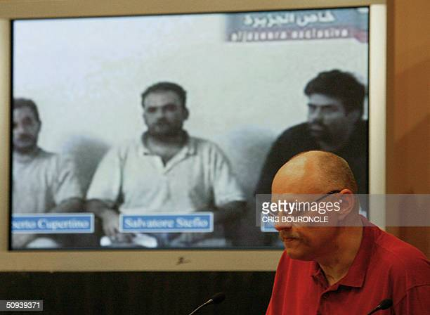 Standing in front a projected image showing three Italian hostages from left to right Umberto Cupertino Salvatore Stefio and Maurizio Agliana Polish...