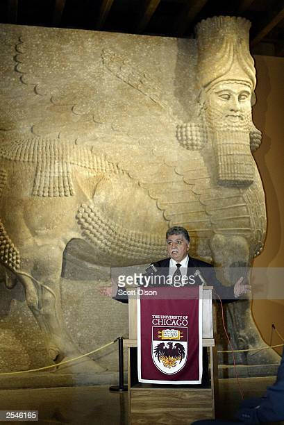 Standing in front of a colossal humanheaded winged bull which once stood at the entrance of the throne room of King Sargon II in Khorsabad capital of...