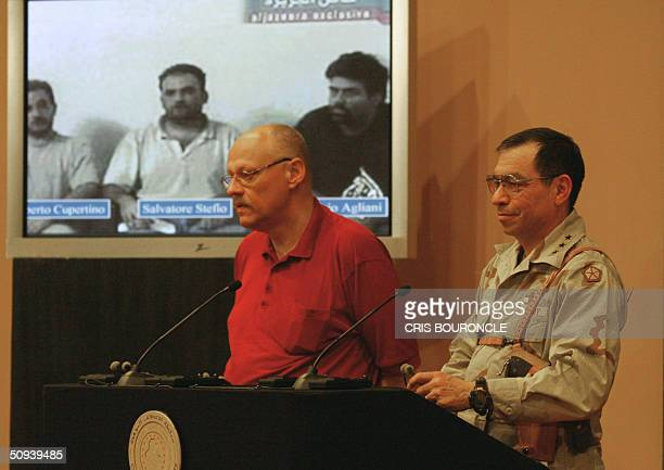 Standing in front of a projected image showing the three Italian hostages from left to right Umberto Cupertino Salvatore Stefio and Maurizio Agliana...