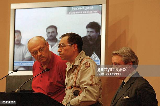 Standing in front of an image showing the three Italian hostages from left to right Umberto Cupertino Salvatore Stefio and Maurizio Agliana US...