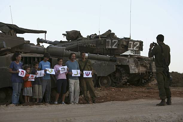 standing in front of an israeli tank an israeli soldiers family hold a happy new year