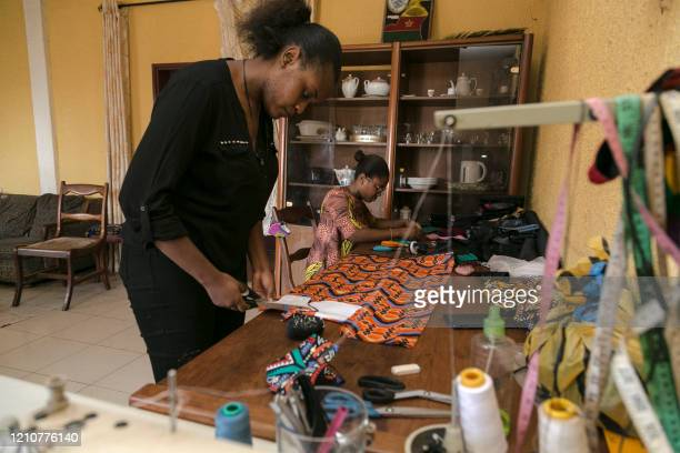 Standing in front of her sewing table, Sheila Notewo, a young Cameroonian woman, cuts African fabric to make a face mask in Yaoundé on April 23,...