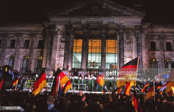 Standing in front of the Reichstag revelers wave German flags and celebrate the reunification of East and West Germany Berlin Germany October 15 1990