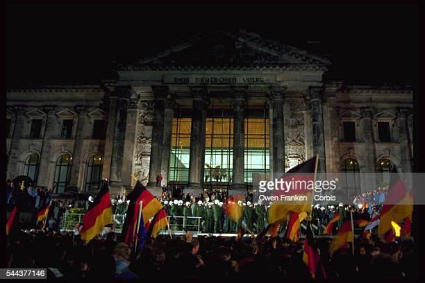 Standing in front of the Reichstag, revelers wave German flags and celebrate the reunification of East and West Germany. Berlin, Germany. October...
