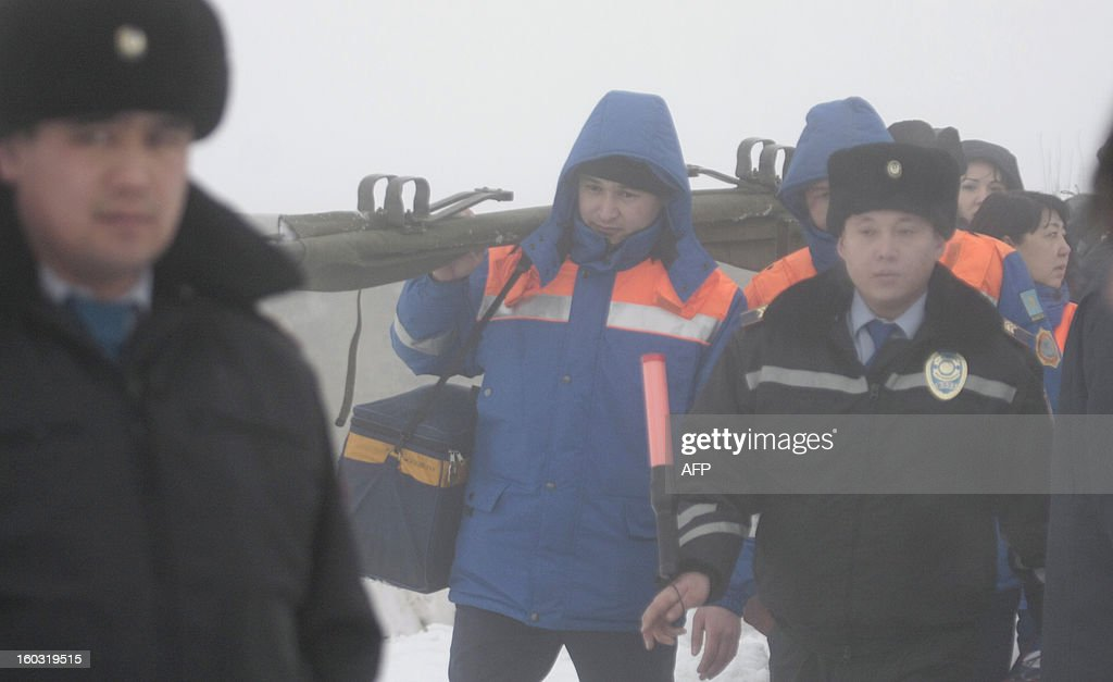 Standing in thick fog Kazakh Interior Ministry officers and paramedics crowd near the site of the plane crash some 30 km outside the Kazakhstan's commercial capital of Almaty, on January 29, 2013. A passenger plane crashed today in thick fog near Almaty killing all 22 people on board, an emergencies services official said.
