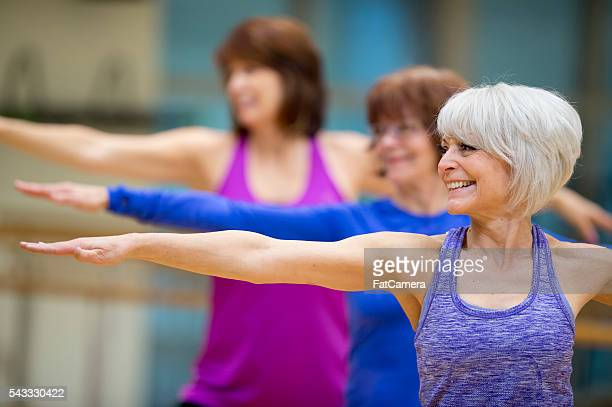 standing in warrior ii pose - active senior woman stock photos and pictures