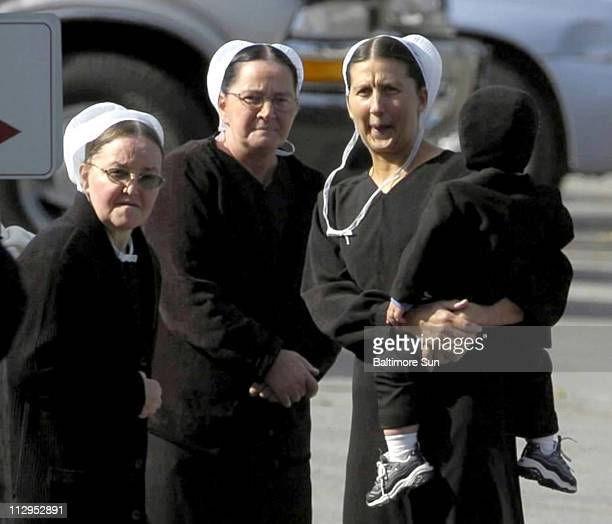 Standing near the entrance of the Georgetown firehouse a group of Amish women take a look at the scene where hundreds of members of the press have...