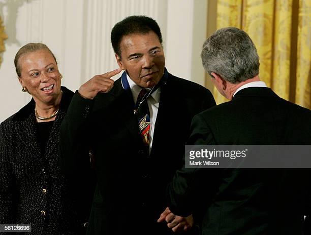 Standing next to his wife Lonnie former heavy weight boxing champion Muhammad Ali points to his head after recieving the Medal of Freedom from US...