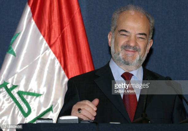 Standing next to the national flag Iraqi Prime Minister Ibrahim Jaafari smiles as he speaks during a press conference 23 August 2005 in Baghdad's...