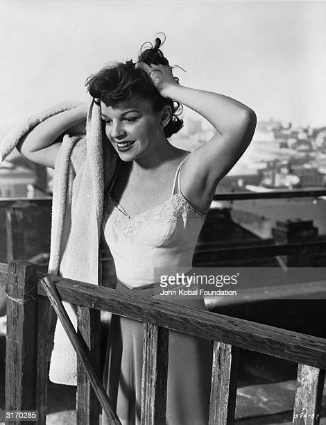 Standing on a rooftop stripped down to an underslip and skirt, Judy Garland dries her hair with a towel in a scene from the film 'A Star Is Born',...