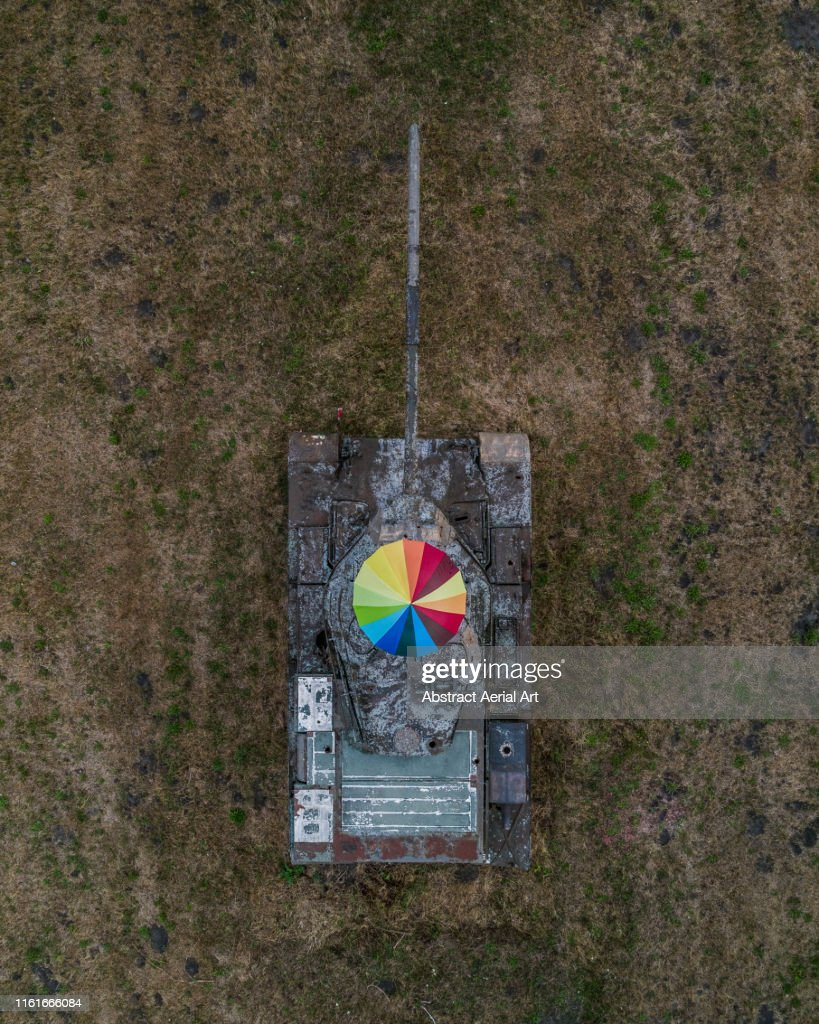 Standing on an abandoned tank holding rainbow coloured umbrella, Germany : Stock Photo