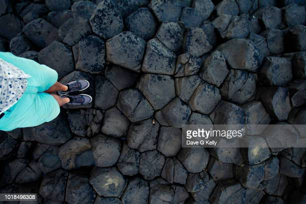 standing on dark volcanic rock - volcanic rock stock pictures, royalty-free photos & images