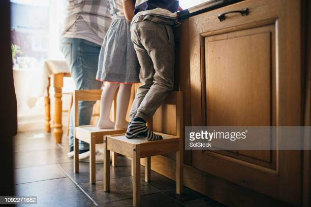 standing on stools to reach the sink - chores stock photos and pictures