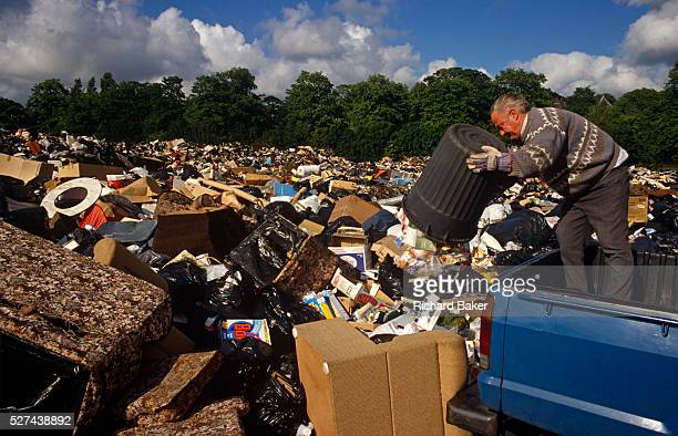 Standing on the back of his utility vehicle a man empties the contents of his dustbin onto a growing pile of rubbish in a recreation park in the...