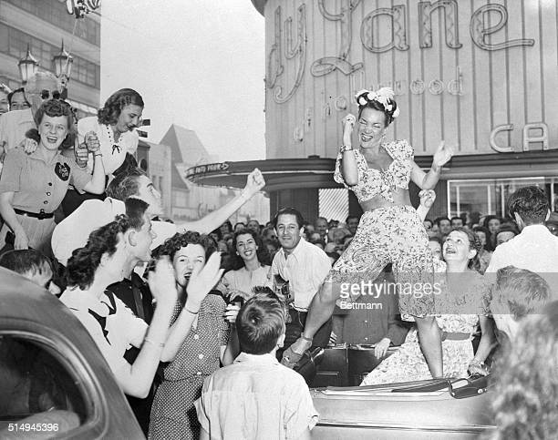 Standing on the back seat of a car actress Carmen Miranda puts her all into one of those Miranda dances as she joins with others of the Hollywood...