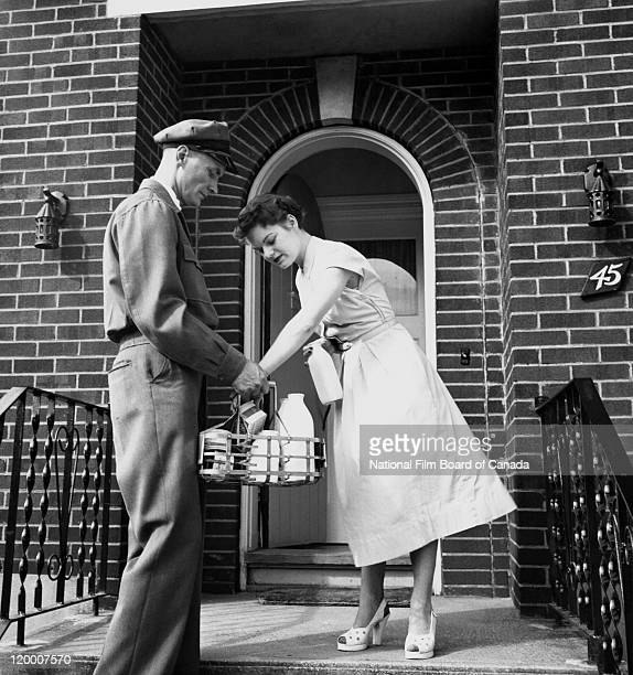 Standing on the porch of a house a woman is taking a bottle of milk from a basket full of dairy products held by a milkman Canada 1947 Photo taken...