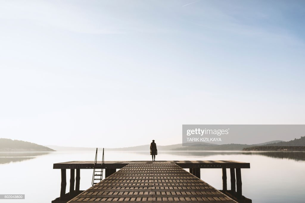 Standing on the seaside jetty : Stock Photo