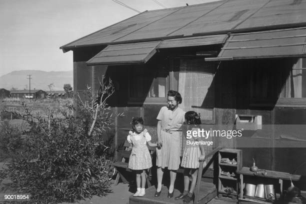 Standing on the step at the entrance of a dwelling, left to right: Louise Tami Nakamura, holding the hand of Mrs. Naguchi, and Joyce Yuki Nakamura....