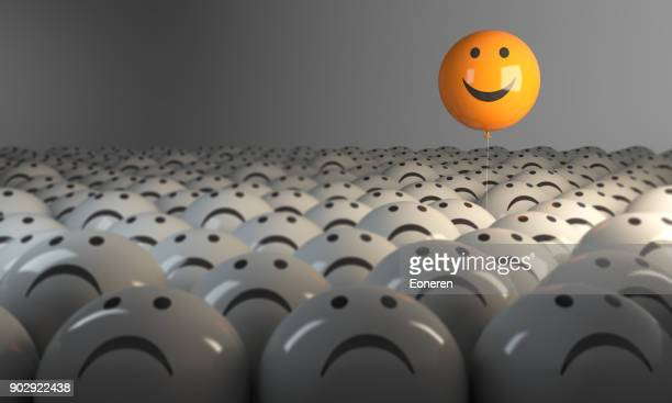 standing out from the crowd with smiling sphere - negative emotion stock pictures, royalty-free photos & images