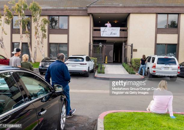 Standing outside their cars people listen as Rev. Robert A. Schuller, top, gives a sermon during a drive-in church service in Santa Ana on Sunday,...