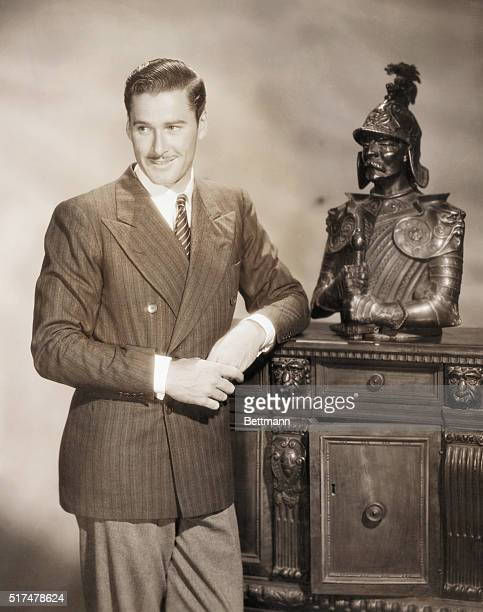 Standing portrait of a youthful Errol Flynn standing by a cabinet with a statue on the top He is wearing a suit and tie and is smiling Flynn starred...