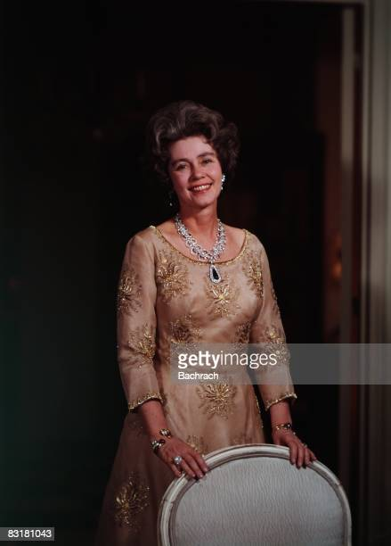 Standing portrait of the Dowager Queen of Greece, Queen Frederika of Hanover . She smiles while standing behind a chair, New York, 1961.