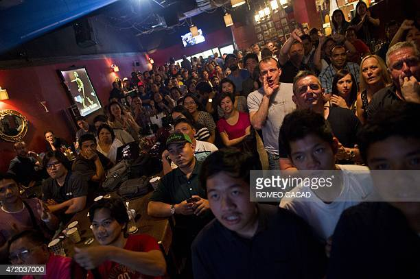 A standing room crowd of Filipinos Indonesians and other foreigners cheer Filipino boxer Manny Pacquiao while watching a live telecast of the...