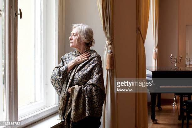 standing senior Frau Blick aus dem Fenster