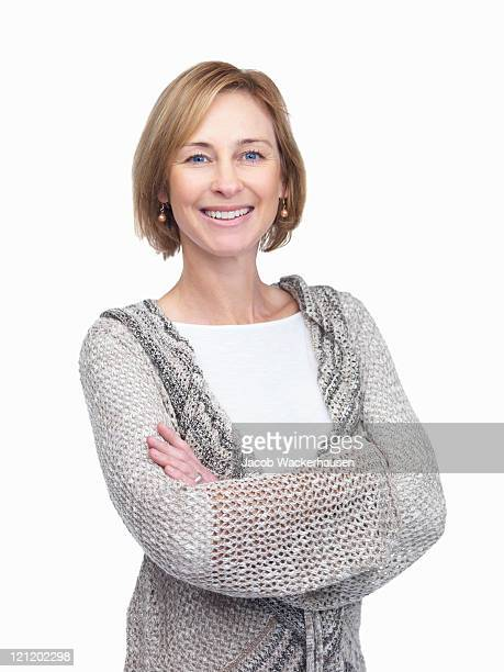 a standing, smiling mature woman with arms folded - 40 44 years stock pictures, royalty-free photos & images